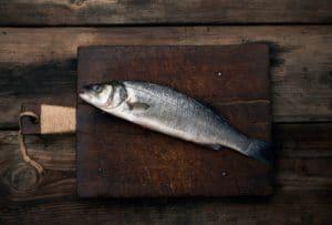 fresh whole sea bass fish on brown wooden cutting board